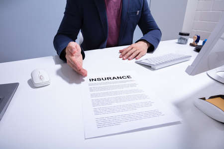 Mid Section Of A Businessman Showing Insurance Document Over White Desk At Office Stock Photo