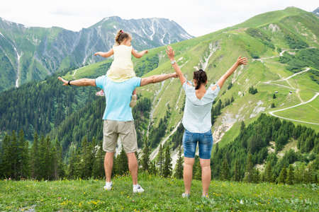 Rear View Of Happy Family Looking At Panoramic Mountain View