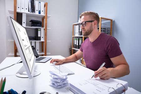 Close-up van een zakenman die de factuur op de computer controleert Stockfoto