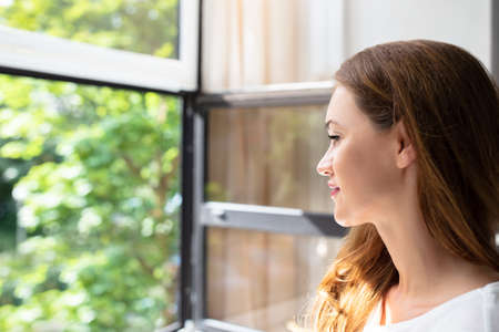 Side View Of Smiling Young Woman Looking Through Window At Home