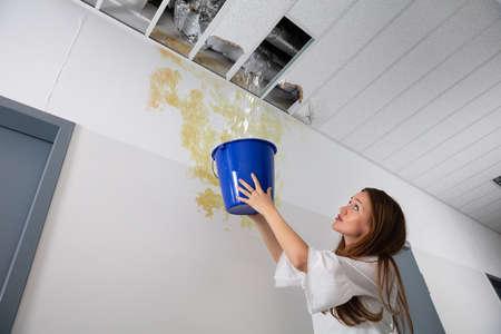 Worried Woman Holding A Blue Bucket Under The Leak Ceiling In Corridor