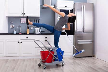 Close-up de una mujer joven deslizándose mientras trapear el piso en la cocina