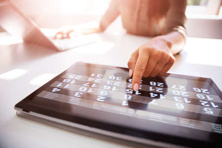 Midsection of businesswoman using calendar on digital tablet in office