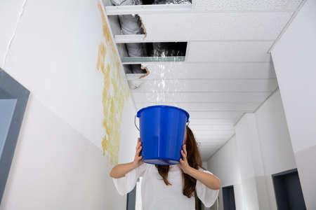 Femme inquiète tenant un seau bleu sous le plafond de fuite dans le couloir