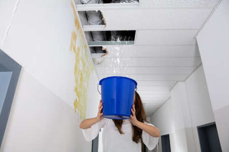 Worried Woman Holding A Blue Bucket Under The Leak Ceiling In Corridor