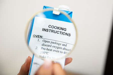 An Elevated View Of Person's Hand Holding Magnifying Glass Over Cooking Instructions On Packaging