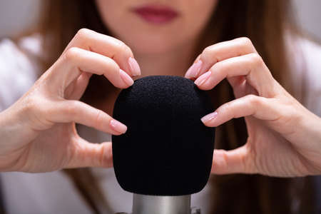 Woman scratching microphone with nails to make ASMR sounds Foto de archivo