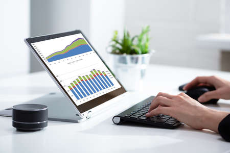 Close-up Of Businesswoman Analyzing Graph On Laptop At Workplace In The Office