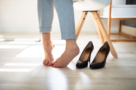 Close-up de la pierna de una mujer cerca de tacones altos sobre un piso de madera Foto de archivo