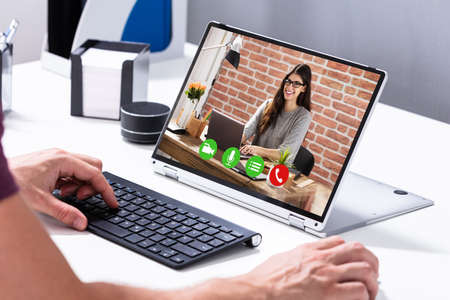 Businessman Video Conferencing With His Colleague On Hybrid Laptop On Desk In Office Archivio Fotografico