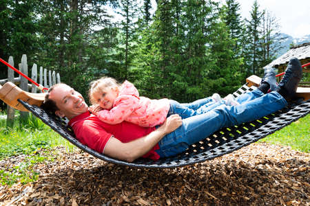 Father And Little Girl Relaxing In Hammock In Mountains