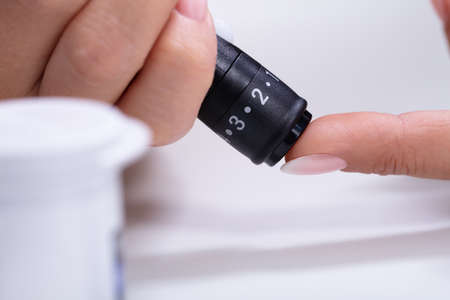 Close-up Of A Womans Hand Testing High Blood Sugar With Glucometer