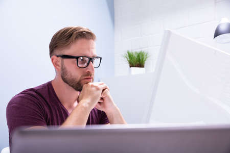 Close-up Of Contemplated Businessman Looking At Computer