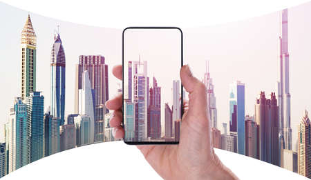 Close-up Of Humans Hand Using Mobile Phone To Capture City Buildings In New York