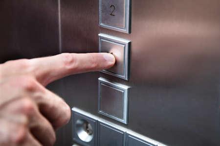 Close-up van menselijke vinger die op de liftknop drukt Stockfoto
