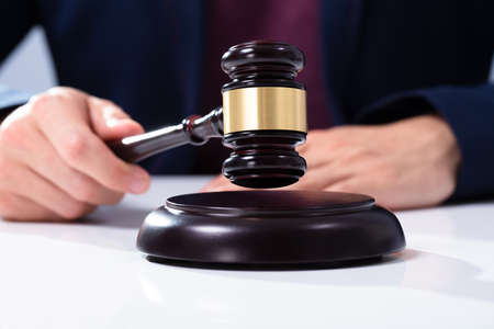 Judge's Hand Striking The Gavel On Sounding Block Over White Desk In Courtroom
