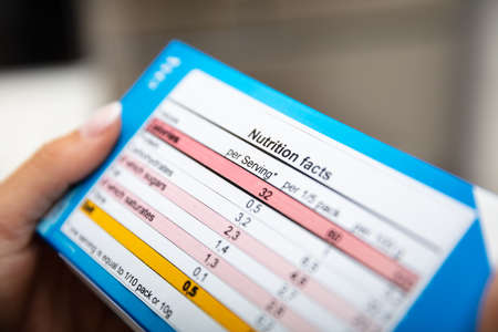 Close-up Of Woman Reading Nutrition Facts On Box Stockfoto