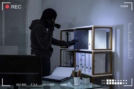 Thief Wearing Balaclava Stealing File From Shelf At Workplace Scene Through CCTV Camera Standard-Bild