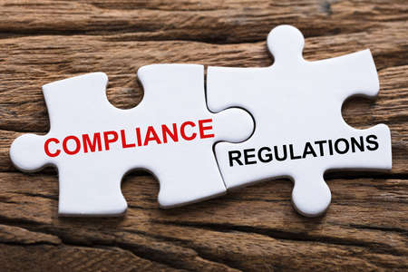 An Elevated View Of Compliance And Regulations Word Written On Pieces Of Jigsaw Puzzle