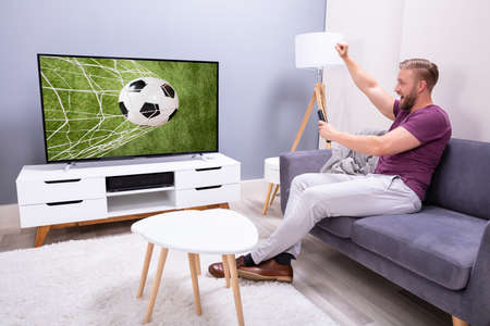 Man Sitting On Couch Watching Soccer Game On Television At Home Stock Photo