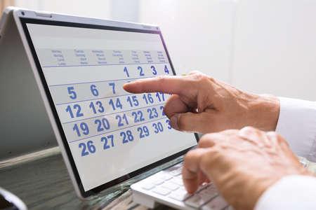 Businessman Looking At Calendar With Daily Agenda Foto de archivo