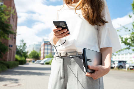 Closeup Of Woman Holding Mobile Phone And External Battery