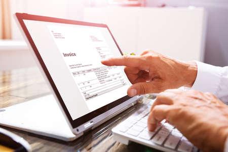 Close-up de la mano de un empresario analizando la factura en el portátil en el lugar de trabajo