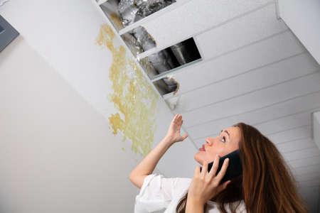 Sad Woman Calling Plumber While Looking At Leak Ceiling In Corridor