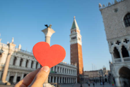 Hand Holding Heart In Front Of Tower Of Saint Mark's Basilica On Piazza San Marco