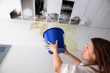 Worried Woman Holding A Blue Bucket Under The Leak Ceiling In Corridor 版權商用圖片