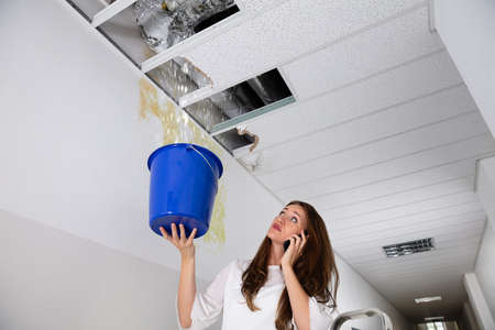 Sad Woman Calling Plumber While Holding Blue Bucket Under The Leak Ceiling In Corridor