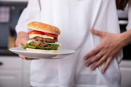 Mid-section Of Woman Suffering From Stomach Pain While Having Burger