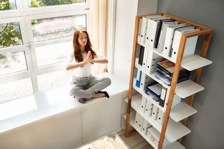 Businesswoman Sitting Over Cabinet Meditating In Office Banco de Imagens - 128458771