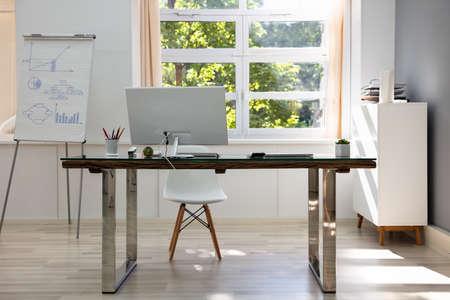 Computer On Desk In Modern Office Interior