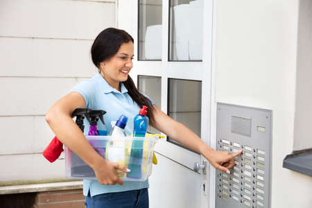 Side View Of Happy Woman Holding Basket Pressing Button Of Intercom To Enter Home Reklamní fotografie