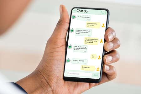 Close-up de mujer con aplicación de bot de chat para chatear en el teléfono inteligente