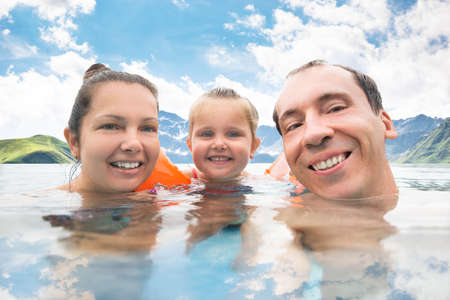 Family Taking Selfie In Swimming Pool In Mountains