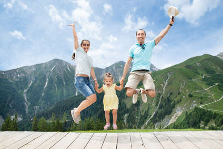 Happy Family With Little Girl Jumping In Austrian Mountains In Summer