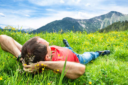 Man Relaxing Lying In Field Of Grass In Mountains