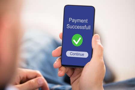 Zbliżenie dłoni osoby pokazującej pomyślną płatność na ekranie telefonu komórkowego