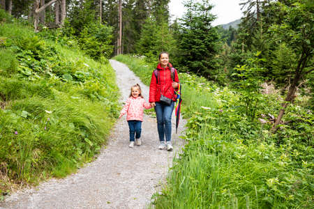 Mother And Little Girl Walking Hiking Trail In Mountains