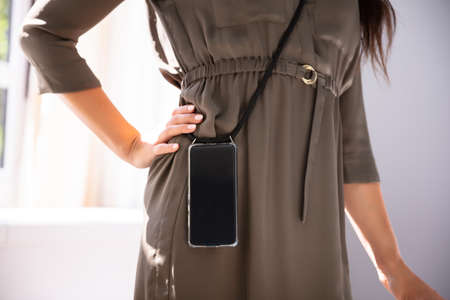 Mid-section Of Woman Carrying Mobile Phone In Office Imagens