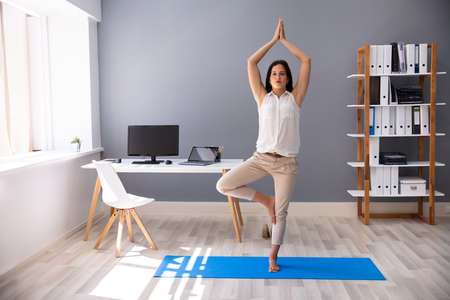 Young Businesswoman Doing Yoga At Workplace In Office