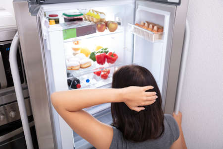 Confused Woman Searching For Food In An Open Refrigerator Imagens