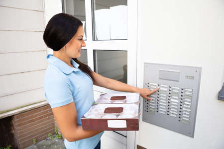 Donut Delivery Woman In Blue Uniform Carrying Boxes Pressing Button Of Intercom To Enter Home