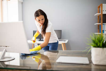 Side View Of Female Janitor Cleaning Desk With Blue Napkin In Office
