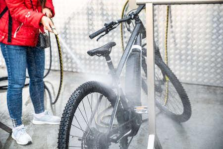 Frau wäscht Mountainbike mit Hochdruckwasserspray