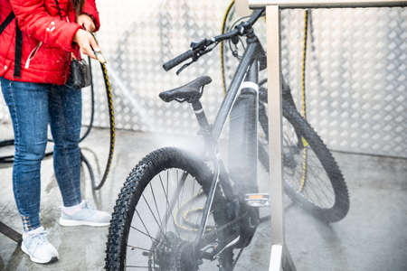 Vrouw wassen mountainbike met hogedruk waternevel