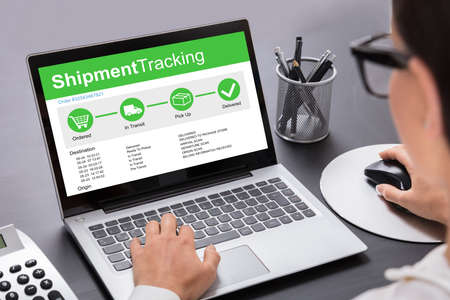 Close-up Of Businesswoman Working On Laptop Showing Shipment Tracking Options On Desk Imagens