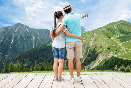 Young Couple Enjoying Panoramic Mountain View In Austria Imagens